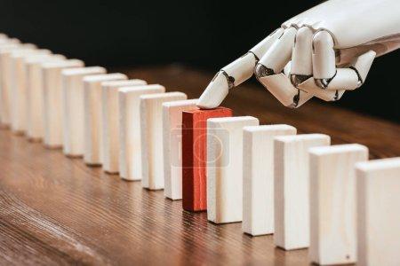 Photo pour Mise au point sélective de main robotisée cueillette rouge brique en bois de rangée de blocs sur le bureau - image libre de droit