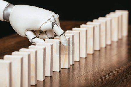 selective focus of robotic hand picking wooden brick from row of blocks on desk