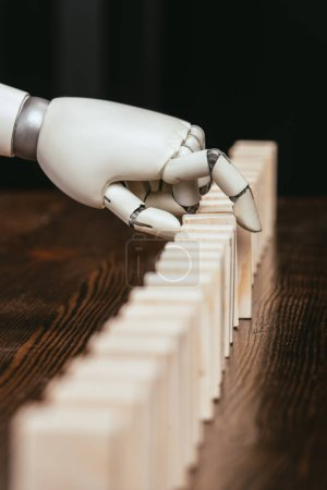 Photo for Selective focus of robotic hand picking wooden brick from row of blocks on desk - Royalty Free Image