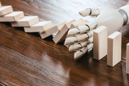 Photo pour Main robotisée empêchant des blocs de bois de tomber sur le bureau avec espace de copie - image libre de droit