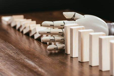 selective focus of robotic hand preventing wooden blocks from falling on desk