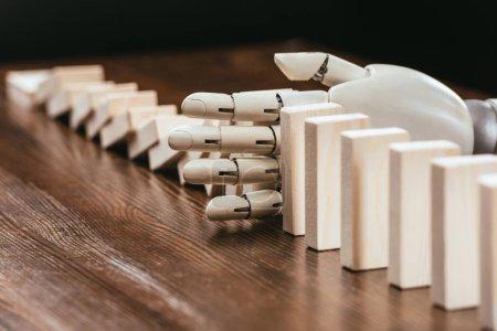Photo pour Mise au point sélective de main robotisée empêchant des blocs de bois de tomber sur le bureau - image libre de droit