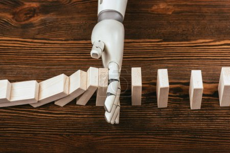 Photo for Robotic hand preventing wooden blocks from falling on desk - Royalty Free Image