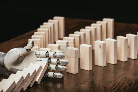 Photo pour Main robotisée empêchant des blocs de bois de tomber sur le bureau isolé sur fond noir - image libre de droit