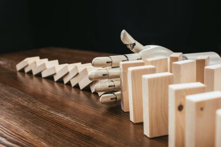 robotic hand preventing wooden blocks from falling on desk isolated on black