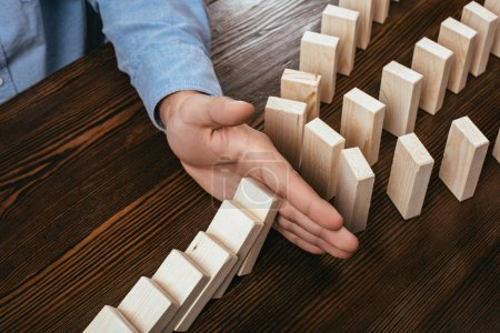 partial view of man preventing wooden blocks from falling on desk