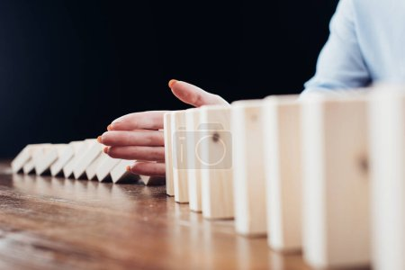 selective focus of woman sitting at desk and preventing wooden blocks from falling