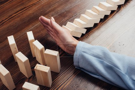 cropped view of woman at desk preventing wooden blocks from falling