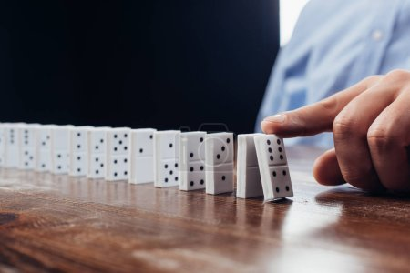 close up view of man pushing domino row on wooden desk