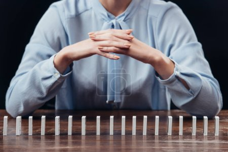 Foto de Vista parcial de la mujer con los brazos cruzados con fila de dominó aislado en negro - Imagen libre de derechos