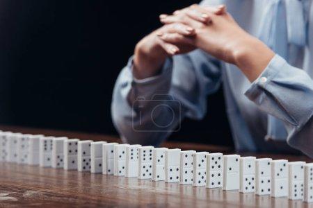 Photo pour Vue partielle de la femme avec les mains jointes avec rangée de domino isolé sur fond noir - image libre de droit
