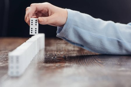 cropped view of woman picking domino from row on wooden desk isolated on black
