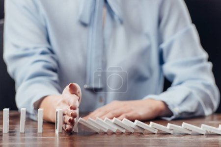 partial view of woman preventing dominoes from falling