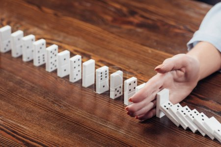 partial view of woman preventing dominoes from falling on wooden desk