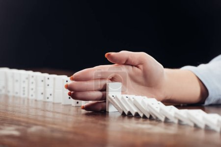 cropped view of woman preventing dominoes from falling on desk isolated on black