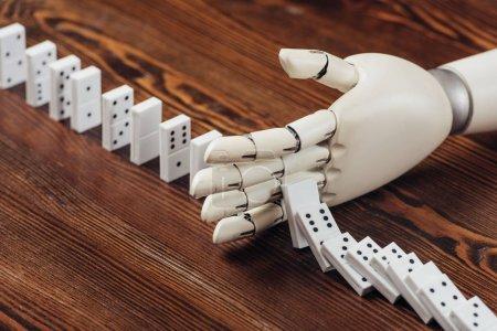 Foto de Enfoque selectivo de mano robótica impidiendo que fichas de dominó cayendo sobre el escritorio de madera - Imagen libre de derechos