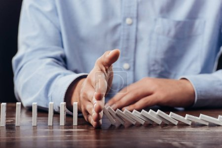 partial view of man preventing dominoes from falling on desk