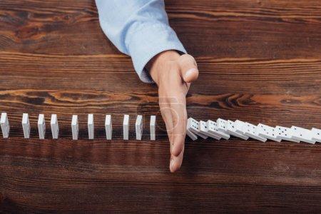 vue de dessus de l'homme, empêchant les dominos de tomber sur le bureau en bois