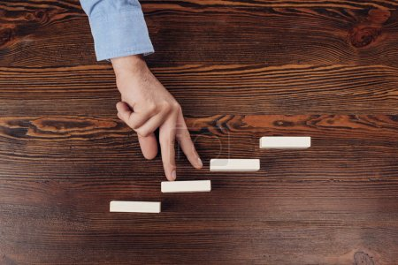 Photo for Cropped view of man walking with fingers on wooden blocks symbolizing career ladder - Royalty Free Image