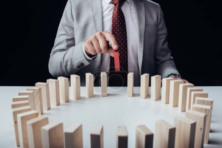 partial view of businessman picking wooden red brick from circle of blocks on desk isolated on black