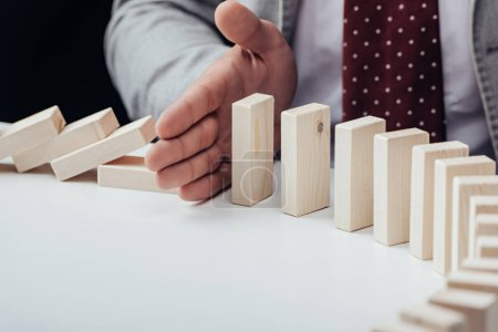 Photo for Close up view of businessman preventing wooden blocks from falling with copy space - Royalty Free Image