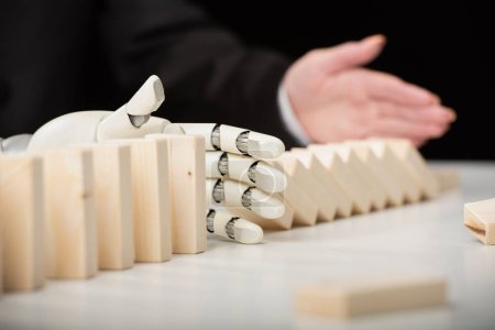 partial view of woman pushing wooden bricks while robotic hand preventing row from falling