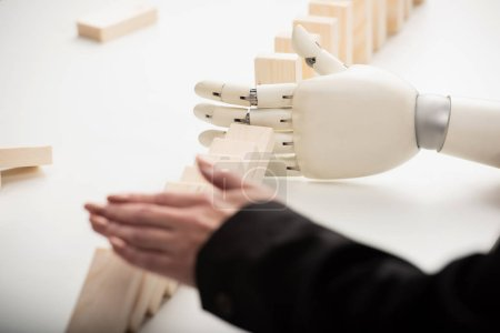 Photo for Cropped view of woman pushing wooden bricks while robotic hand preventing row from falling - Royalty Free Image