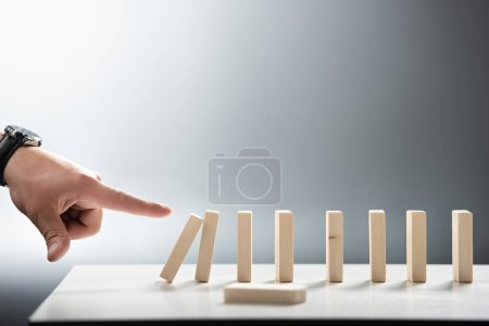 Photo for Cropped view of man pointing with finger at falling wooden block row on grey background - Royalty Free Image