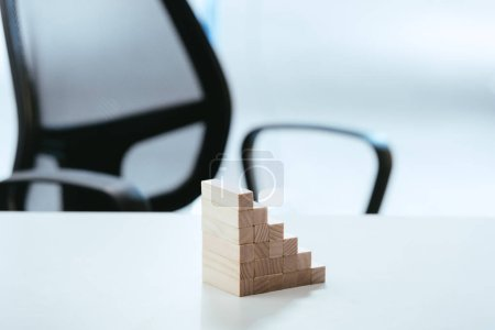 selective focus of wooden blocks symbolizing career ladder on white desk