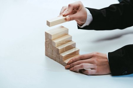 Photo for Cropped view of woman putting wooden brick on top of wooden blocks symbolizing career ladder - Royalty Free Image