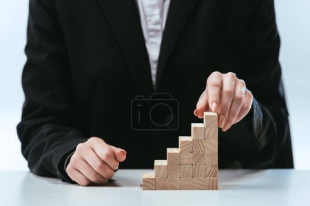 cropped view of woman with wooden blocks symbolizing career ladder