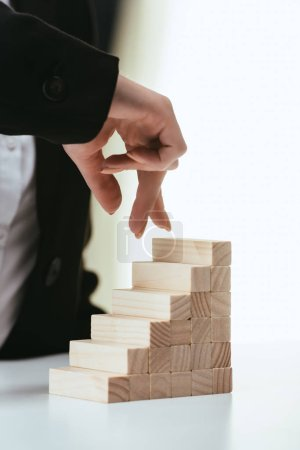 partial view of woman walking with fingers on wooden blocks symbolizing career ladder