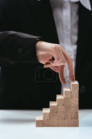 cropped view of woman walking with fingers on wooden blocks symbolizing career ladder