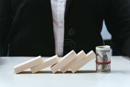 enfoque selectivo de la fila caída de bloques de madera y rollo de dinero con la mujer de negocios en el fondo