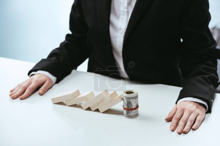 cropped view of businesswoman sitting at table with fallen row of wooden blocks and money roll