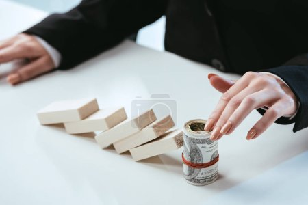 partial view of businesswoman sitting at table with fallen row of wooden blocks and money roll