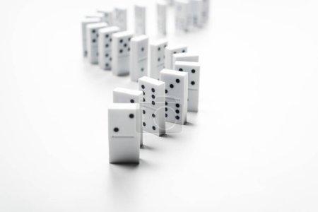 Photo pour Mise au point sélective de rangée de domino isolée sur blanc avec espace de copie - image libre de droit