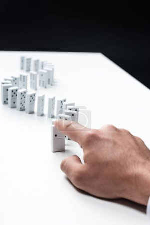 Photo for Partial view of man pointing at domino row on white table - Royalty Free Image