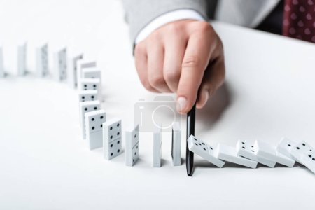 Photo for Close up view of man preventing dominoes from falling with pen - Royalty Free Image