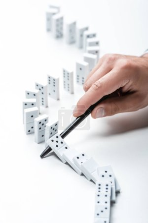 Photo for Partial view of man preventing dominoes from falling with pen on white background - Royalty Free Image