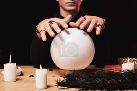 cropped view of man holding hands above crystal ball near candles isolated on black