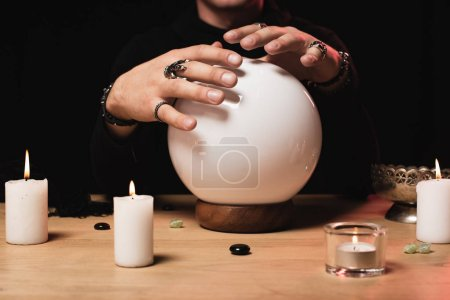 cropped view of esoteric holding hands above crystal ball near candles isolated on black