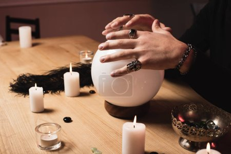 Photo for Cropped view of psychic holding hands above magical crystal ball near candles - Royalty Free Image