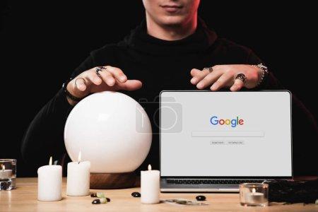 vue recadrée de psychique près ordinateur portable avec google site Web à l'écran isolé sur noir