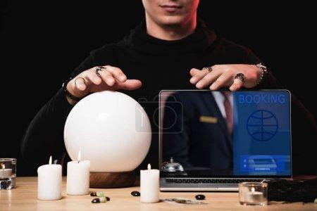 vue recadrée de l'oracle près d'un ordinateur portable avec site de réservation à l'écran isolé sur noir