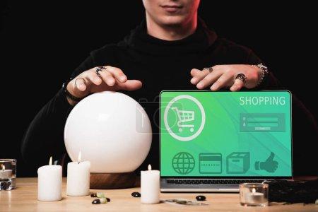 vue recadrée de l'oracle près d'un ordinateur portable avec site de magasinage à l'écran isolé sur noir