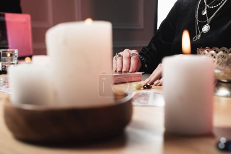 selective focus of  female psychic  laying tarot cards near burning candles
