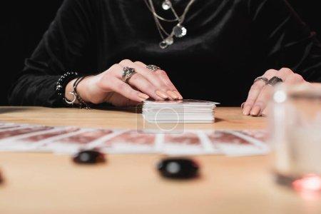Foto de Enfoque selectivo femenino psíquico colocación cartas del tarot junto a piedras de la adivinación - Imagen libre de derechos