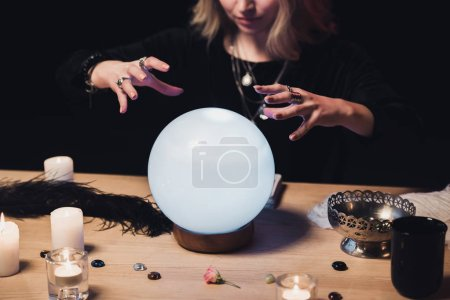 vue recadrée de femmes ésotériques tenant les mains au-dessus de boule de cristal isolé sur noir
