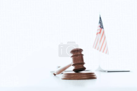 selective focus of wooden gavel with american flag on background  isolated on white